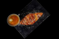 Cup of coffee with croissant on a black background royalty free illustration