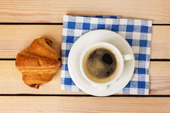 Cup of coffee and a croissant bun on a napkin on a wooden background Stock Images