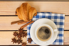 Cup of coffee and a croissant bun on a napkin on a wooden background Royalty Free Stock Photo