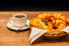 Cup of coffee with croissant and a cake basket in the background. Stock Photography