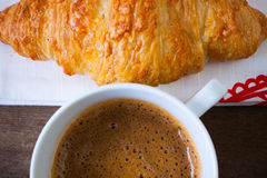 Cup of coffee with a croissant on cloth Stock Photos
