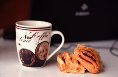 Cup of coffee with croissant and a laptop on background Stock Photography