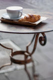Cup of coffee and croissant on metal table. Royalty Free Stock Photography