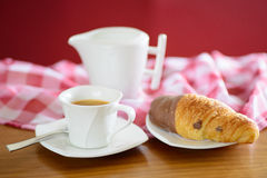 Cup of coffee, croissant and a milk jug Stock Image