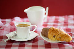 Cup of coffee, croissant and a milk jug Royalty Free Stock Image