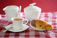Cup of coffee, croissant, a milk jug and a sugar bowl Stock Photo