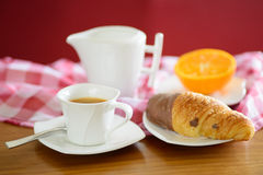 Cup of coffee, croissant, orange and a milk jug Royalty Free Stock Photography