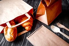 Cup coffee and croissant in paper bag on wooden background Stock Photo