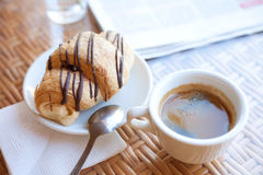 Cup of coffee and a croissant on the table Stock Images