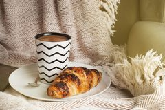 Cup of coffee with croissant on a white plate, with warm blanket. Breakfast, selective focus, toned. Cup of coffee with croissant on a white plate, with warm royalty free stock photos