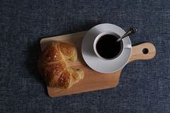Top view of Coffee and croissant. A cup of coffee and croissant on wooden board in blue background Royalty Free Stock Photos