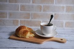Coffee and croissant. A cup of coffee and croissant on wooden board in brick wall background Stock Images