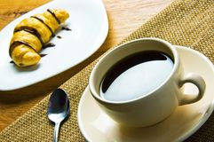 Cup of coffee and a croissant Stock Image
