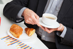 Cup of coffee and croissant at work Royalty Free Stock Photos