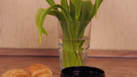 Cup of coffee with croissants. Freshly brewed coffee with buns in the kitchen. Yellow tulips stock video