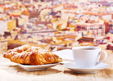 Cup of coffee and croissants over cityscape Stock Photography