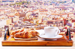 Cup of coffee and croissants over cityscape Stock Photo