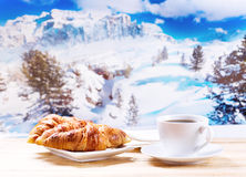 Cup of coffee and croissants over winter landscape. Cup of coffee and croissants on wooden table over winter landscape Royalty Free Stock Images