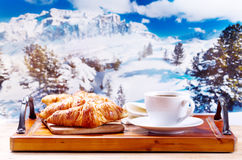 Cup of coffee and croissants over winter landscape Royalty Free Stock Photography