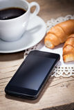 A cup of coffee with croissants and smartphone Stock Photography