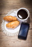 A cup of coffee with croissants and smartphone Royalty Free Stock Image