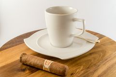 Cup of coffee with cuban cigar beside. Photo of a Cup of coffee with cuban cigar beside stock photo