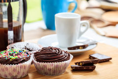 Cup of coffee and a cup cake on a wooden surface. Cup of coffee and a cup cake Royalty Free Stock Photos