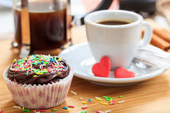 Cup of coffee and a cup cake on a wooden surface Royalty Free Stock Photos