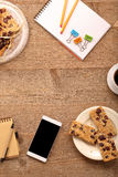 Cup of coffee cup with crunchy cookie on the table and smart pho Royalty Free Stock Photo