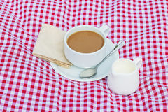 Cup of coffee and cup of milk put on fabric red, white Stock Images