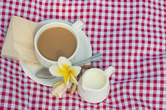Cup of coffee and cup of milk put on fabric red, white Royalty Free Stock Image