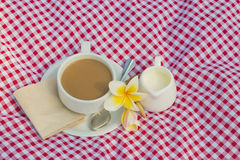 Cup of coffee and cup of milk put on fabric red, white. Have spoon and tissue paper put on saucer. have flower put on saucer Royalty Free Stock Photo