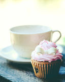 Cup of coffee and cupcake on wooden table. And sunshine Royalty Free Stock Photos