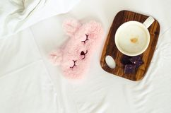 Cup of coffee with cute pink sleep mask. Cup of coffee cappuccino with chocolate and cute pink sleep mask on the bed on cozy lazy sunday. White bedding sheet stock images
