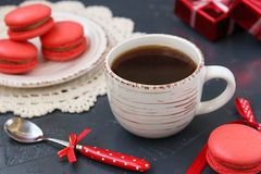 A cup of coffee on a dark background with macaroons of coral color royalty free stock photo