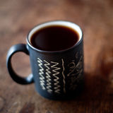Cup of coffee on dark background. Cup of coffee on wooden table. Very shallow depth of field Royalty Free Stock Photography