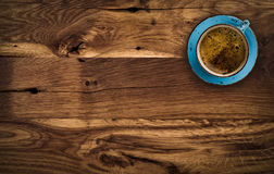 Cup of coffee on dark brown wooden table, above view royalty free stock image