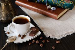 Cup of coffee with dark chocolate on dark background with journal. Small cup of black coffee with vintage teaspoon, turkish coffee pot and chocolate pieces on stock images