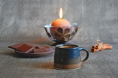 Cup of coffee, dark chocolate, cinnamon sticks and burning decorative candle royalty free stock photography