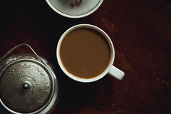 Cup of coffee on dark wooden table. Cup of coffee and a sugar-bowl on dark wooden table Royalty Free Stock Images
