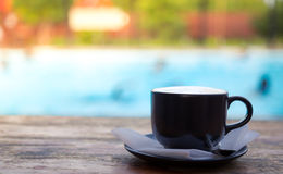 Cup of coffee on  deck near Swimming pool Stock Image