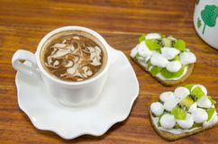 Cup of coffee with decorated foam. And kiwi with cream biscuits Stock Images