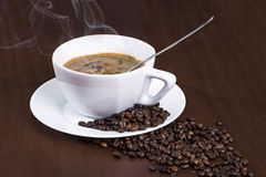 Cup of coffee. The cup of delicious coffee with coffee beans around it Royalty Free Stock Images
