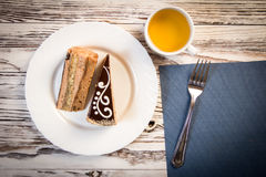 Cup of coffee and delicious cake on wooden table Stock Images