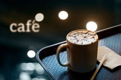 A cup of coffee with design pattern in a white cup on tray and and text cafe in dark background, soft focus Royalty Free Stock Photos