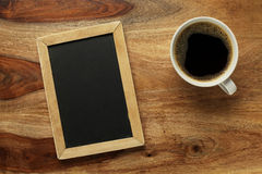 Cup of coffee on desk with chalkboard Royalty Free Stock Photography