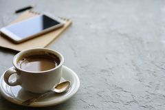 Cup of coffee on desk or workspace. Notebook, planner and phone Royalty Free Stock Photo