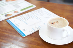 Cup of coffee with dinner menu at background on wood table Stock Photos
