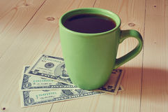 Cup of coffee on dollar bills pile Royalty Free Stock Images