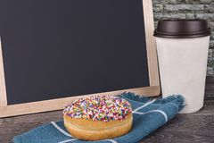 Cup of coffee and donut on an old wooden table. Stock Photo